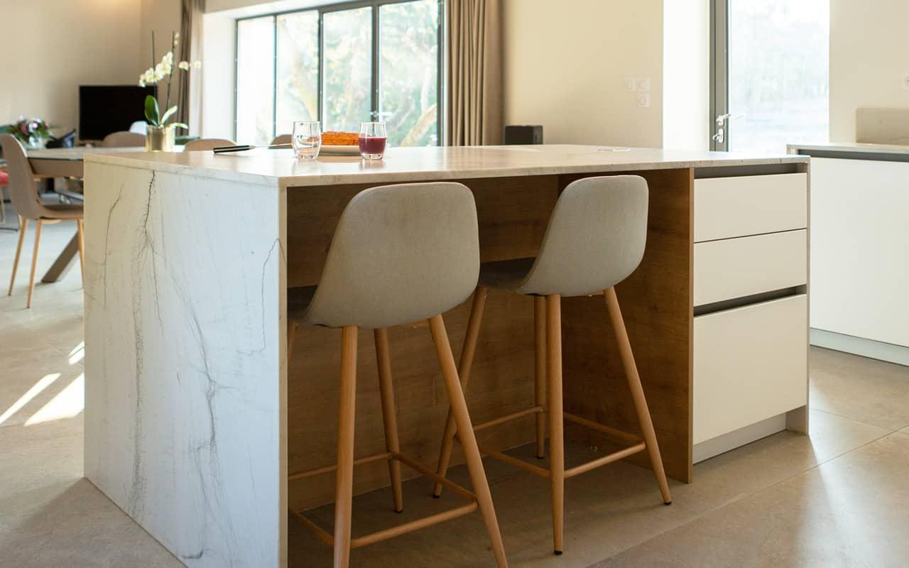 Projet de l'Atelier de Léa : focus sur l'îlot central en marbre d'une cuisine contemporaine minimaliste blanche sur-mesure.