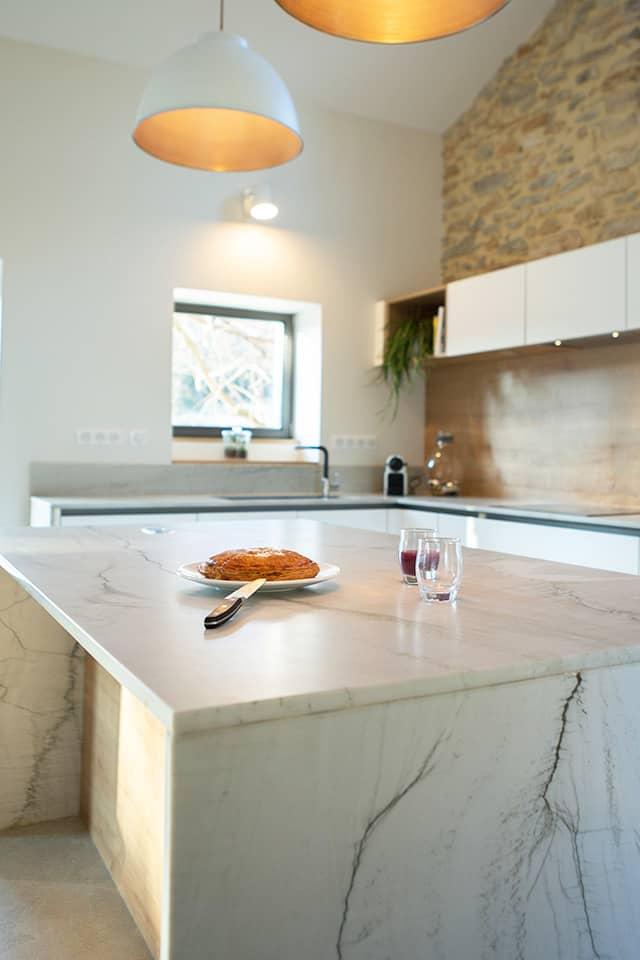 Projet de l'Atelier de Léa : focus sur le plan de travail en marbre d'une cuisine contemporaine minimaliste blanche sur-mesure.