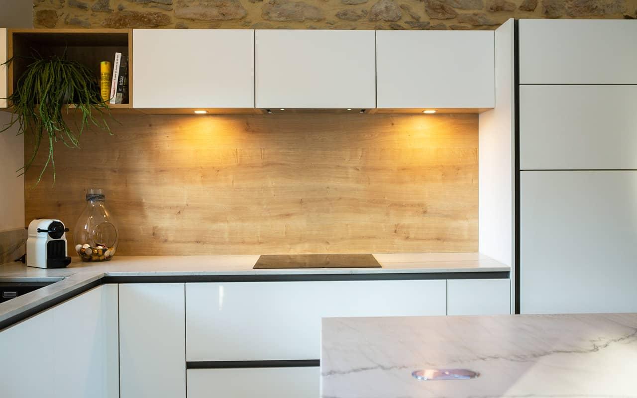 Projet de l'Atelier de Léa : focus sur les placards, la façade en bois et le plan de travail marbre d'une cuisine contemporaine minimaliste blanche sur-mesure.