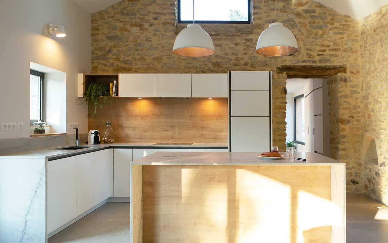 Projet de l'Atelier de Léa : vue frontale d'une cuisine contemporaine minimaliste blanche sur-mesure avec plans de travail en marbre.