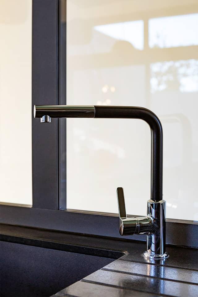 Projet de l'Atelier de Léa : focus sur l'évier d'une cuisine moderne noire sur-mesure en cube avec verrière.