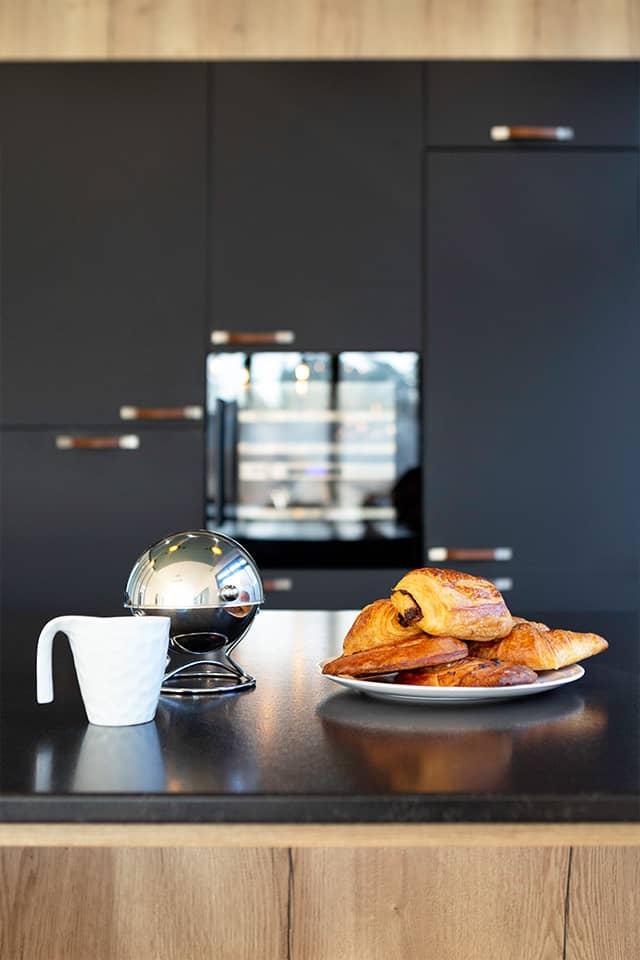 Projet de l'Atelier de Léa : focus sur le plan de travail en granite d'une cuisine moderne noire sur-mesure en cube avec verrière.