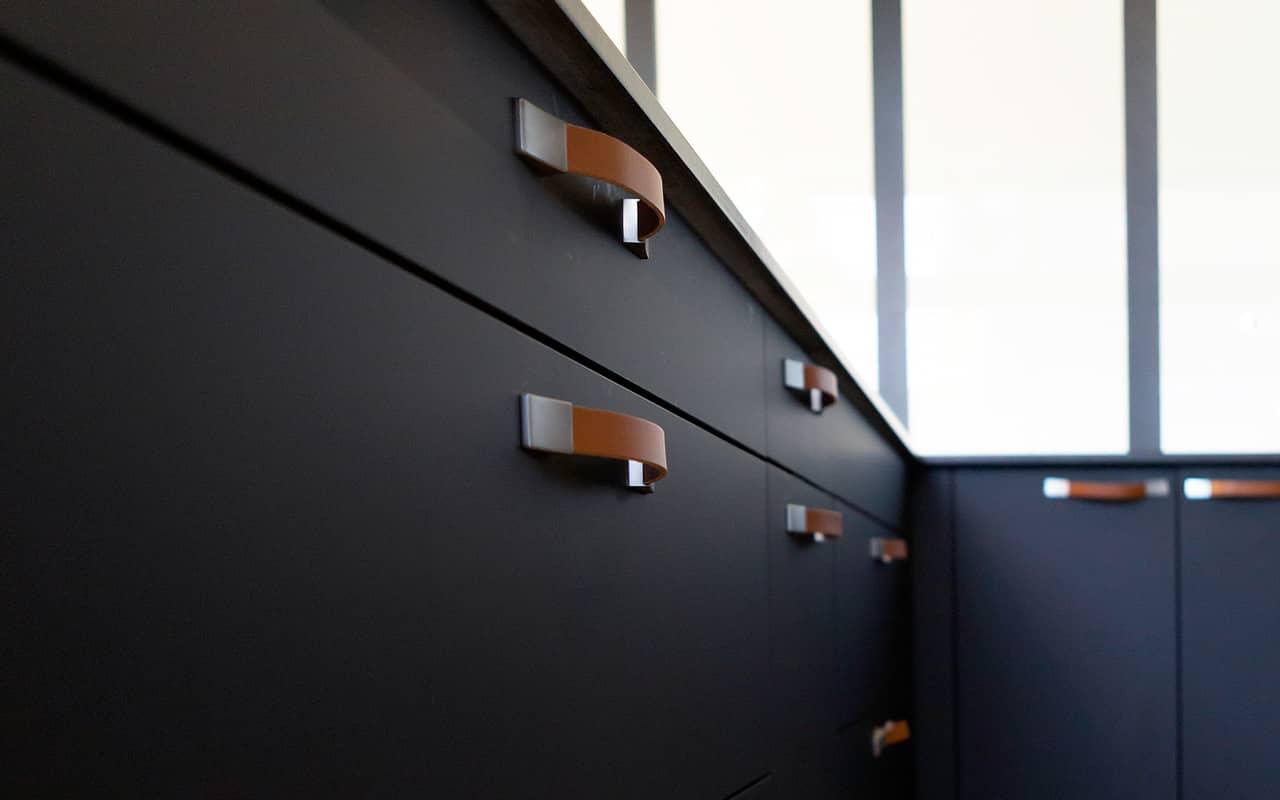 Projet de l'Atelier de Léa : focus sur les façades de placards noires avec poignées en cuir d'une cuisine moderne sur-mesure.