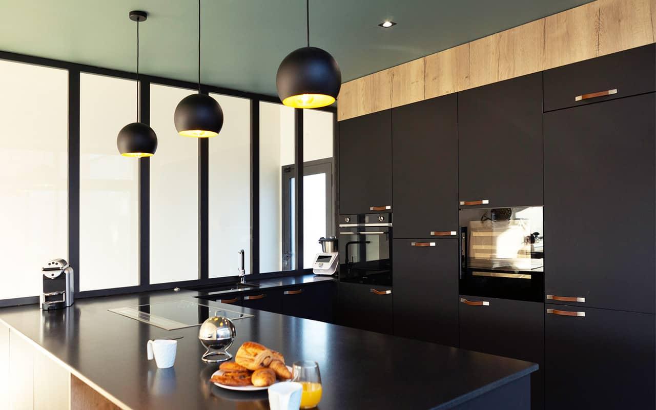 Projet de l'Atelier de Léa : vue en angle d'une cuisine moderne noire sur-mesure en cube avec verrière et plans de travail en granite.