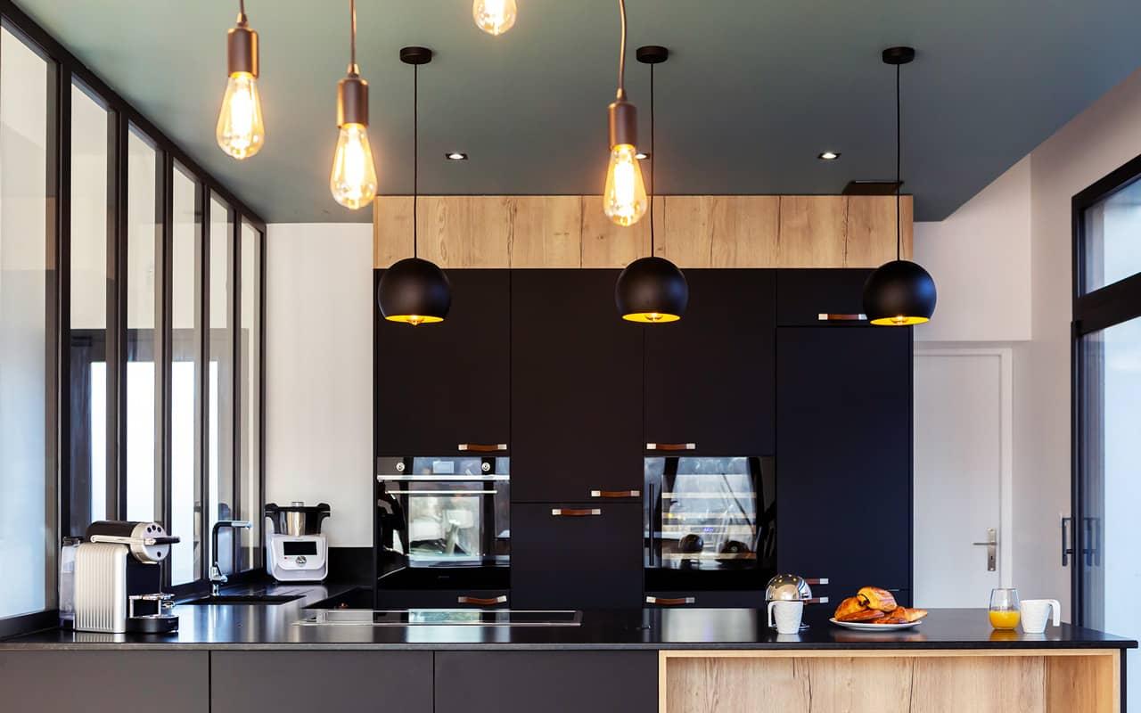 Projet de l'Atelier de Léa : vue frontale d'une cuisine moderne noire sur-mesure en cube avec verrière et plans de travail en granite.