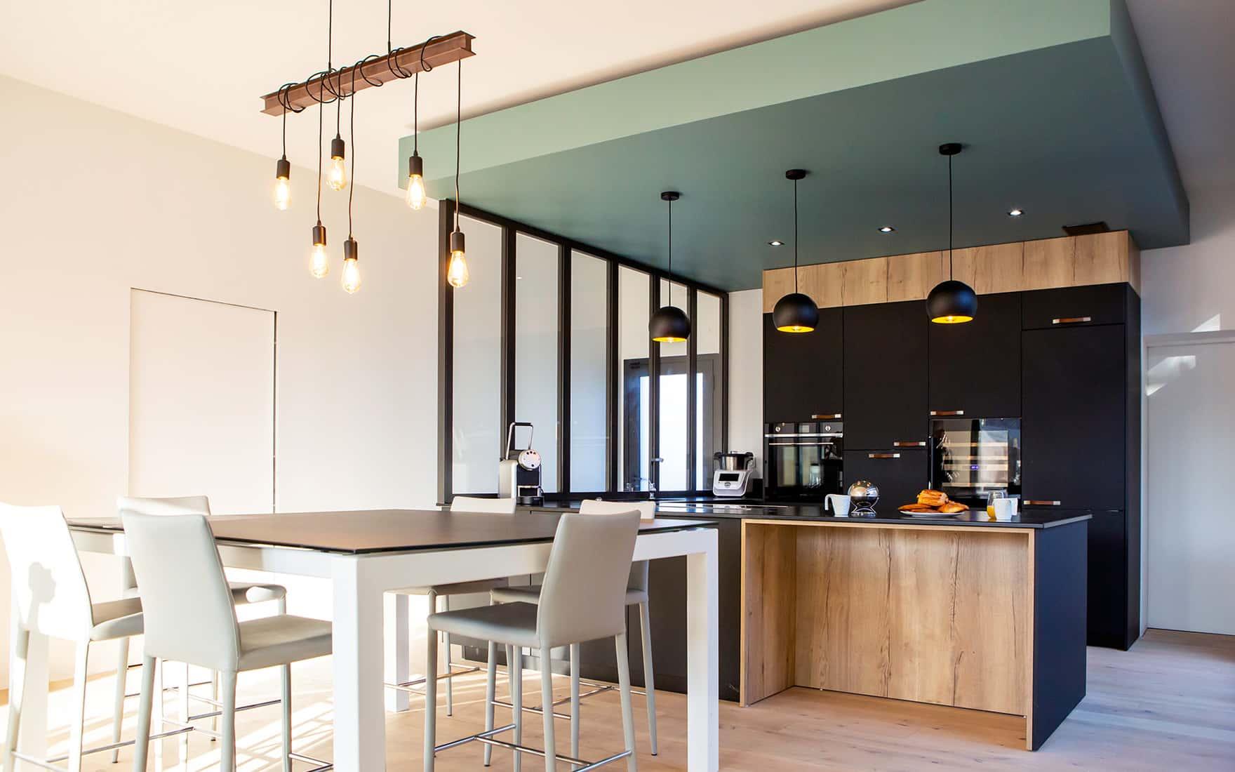 Projet de l'Atelier de Léa : cuisine moderne noire sur-mesure en cube avec verrière et plans de travail en granite.