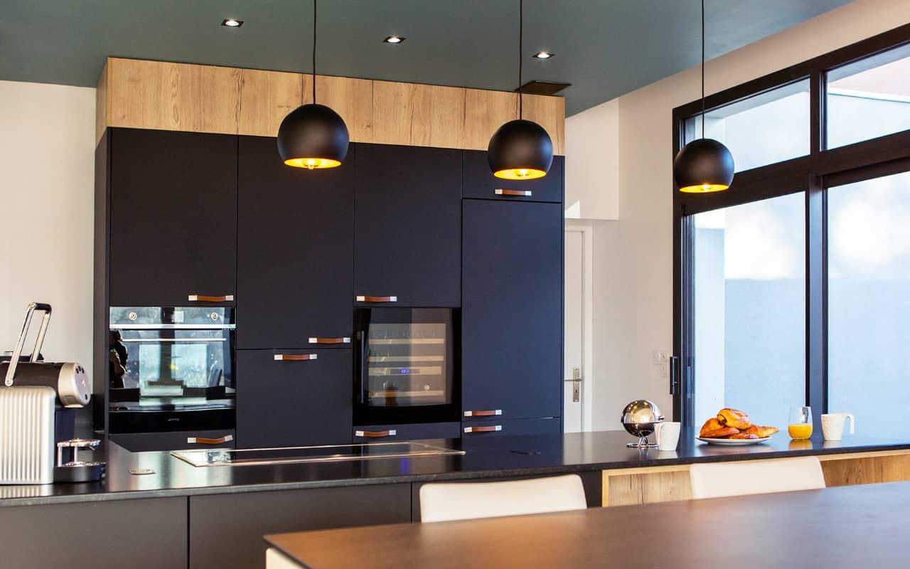 Projet de l'Atelier de Léa : cuisine moderne noire sur-mesure avec plans de travail en granite et poignées en cuir.