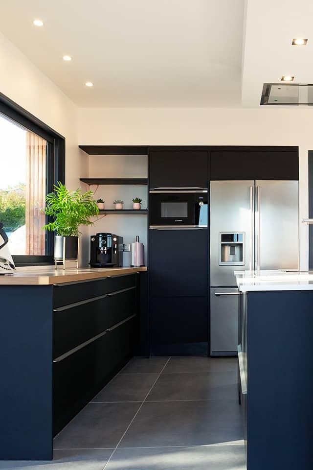 Projet de l'Atelier de Léa : couloir de circulation d'une cuisine moderne noire asymétrique sur-mesure avec plans de travail en bois et granite.
