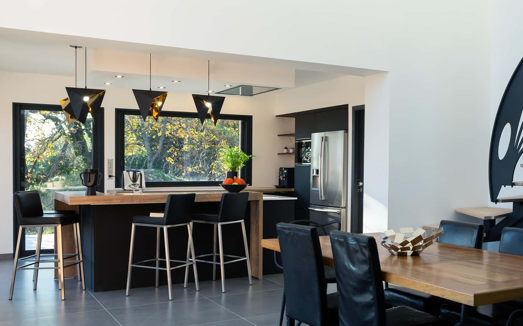 Projet de l'Atelier de Léa : cuisine moderne noire asymétrique sur-mesure avec plans de travail en bois et granite.
