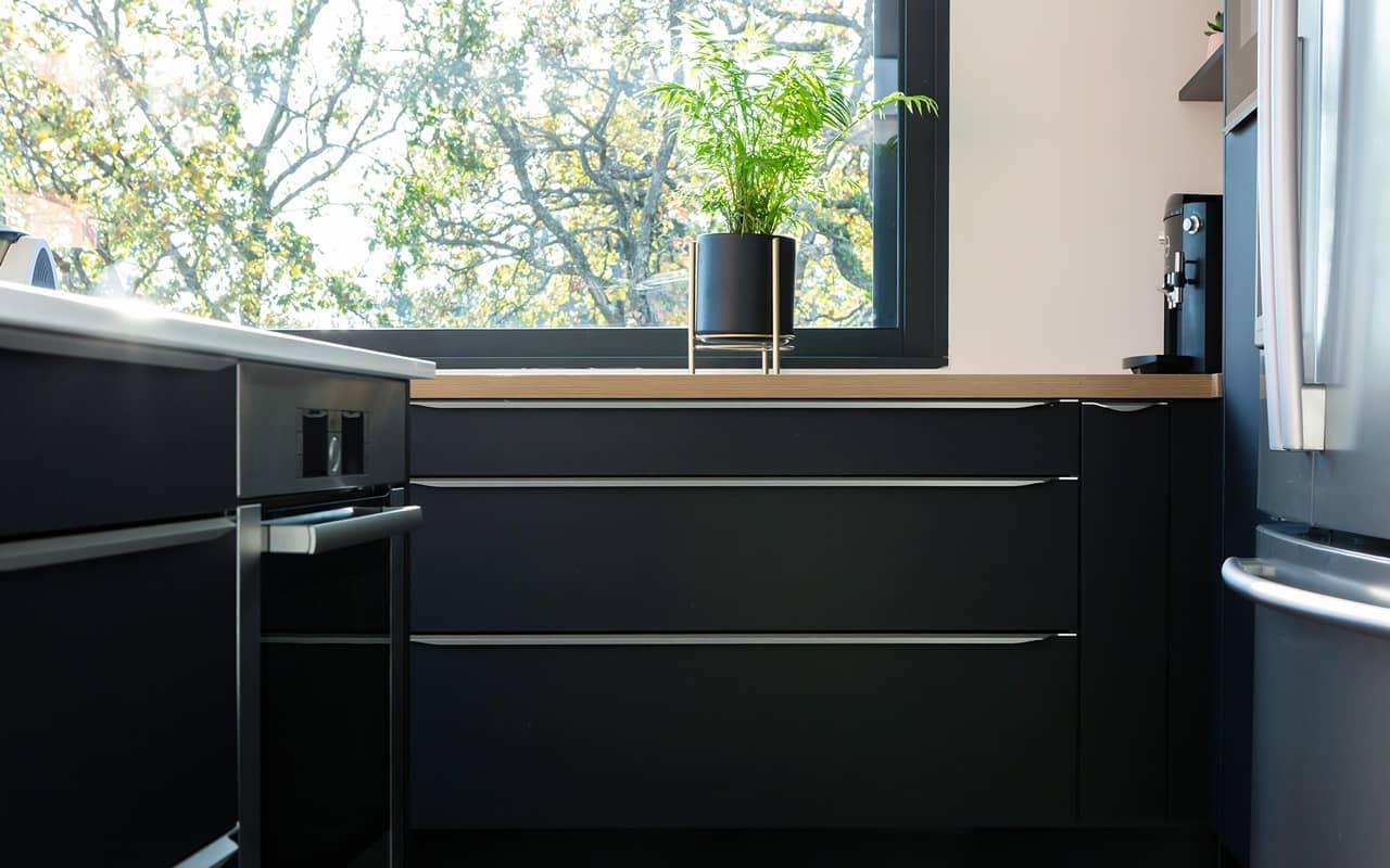 Projet de l'Atelier de Léa : focus sur les façades de placards noires et poignées en acier d'une cuisine moderne asymétrique sur-mesure.