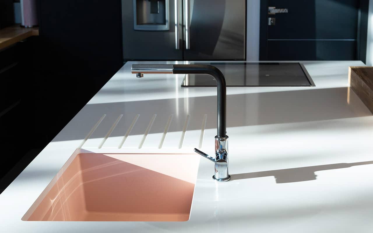 Projet de l'Atelier de Léa : focus sur le plan de travail en granite blanc et évier rose d'une cuisine moderne noire asymétrique sur-mesure.