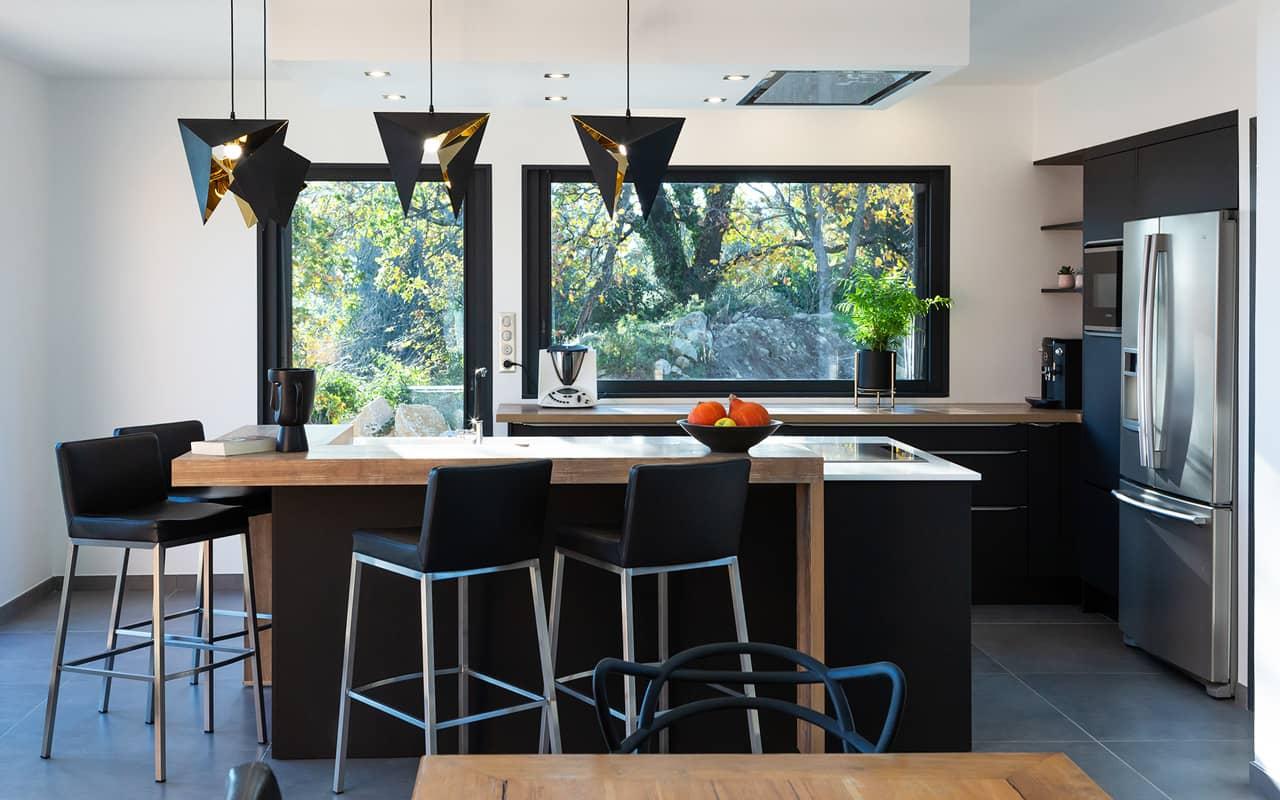 Projet de l'Atelier de Léa : vue frontale d'une cuisine moderne noire asymétrique sur-mesure avec plans de travail en bois et granite.