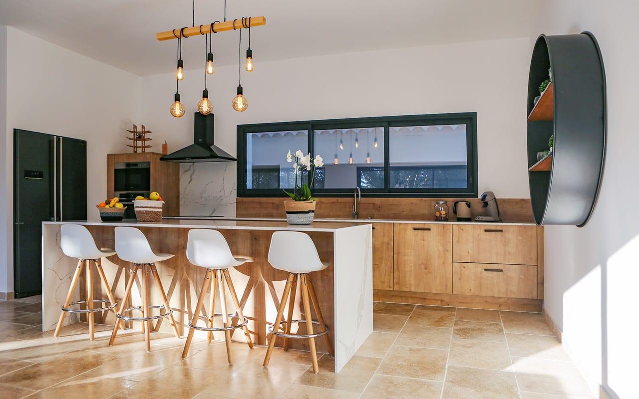 Projet de l'Atelier de Léa : vue en angle d'une cuisine contemporaine sur-mesure, avec façades en bois et plans de travail en marbre.