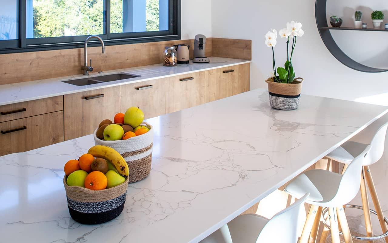 Projet de l'Atelier de Léa : focus sur un grand îlot en marbre d'une cuisine contemporaine.