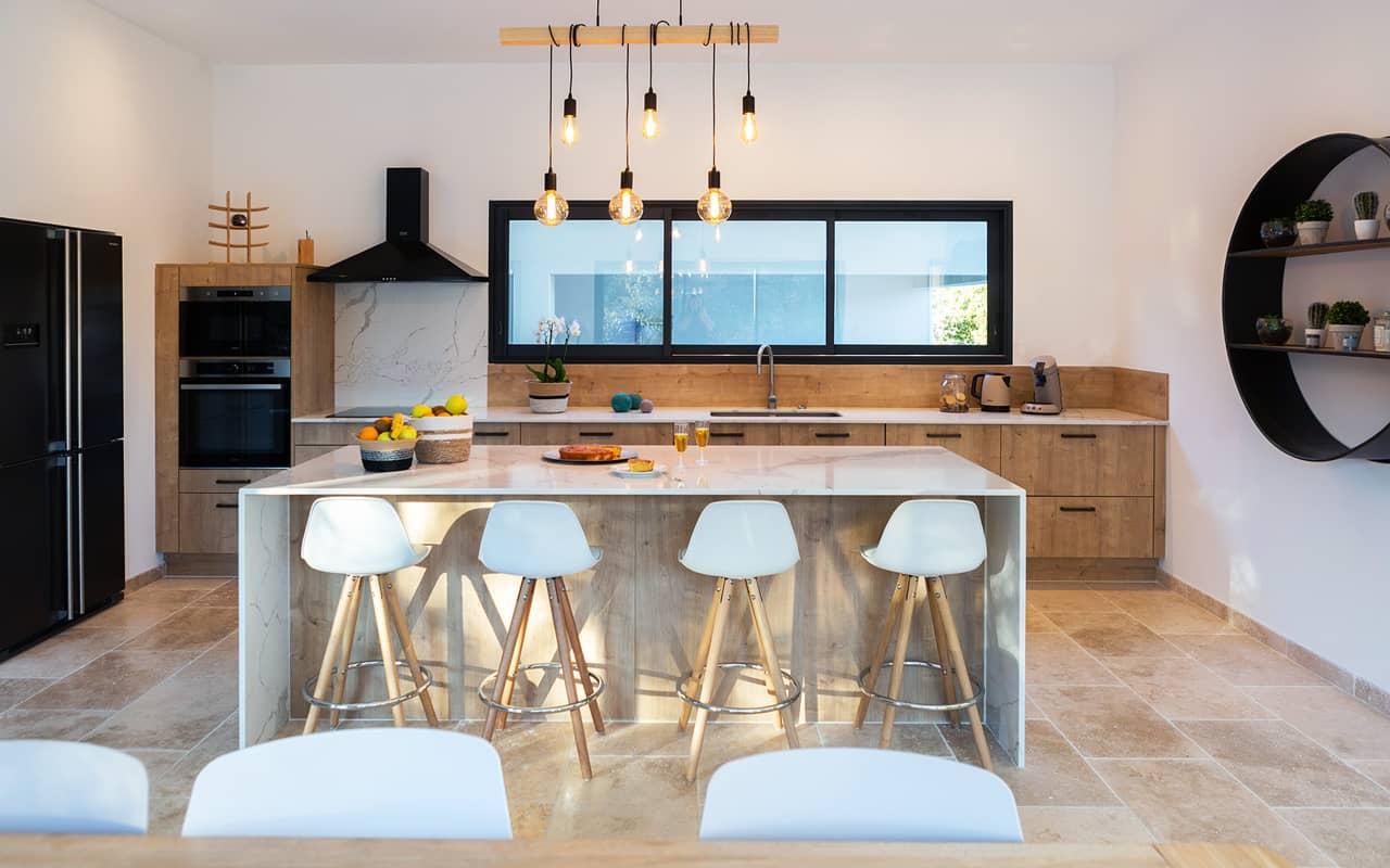 Projet de l'Atelier de Léa : vue frontale d'une cuisine contemporaine sur-mesure, avec façade en bois et plans de travail en marbre.