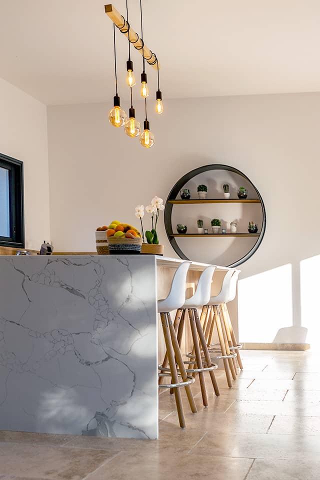 Projet de l'Atelier de Léa : focus sur l'îlot en marbre d'une cuisine contemporaine sur-mesure.