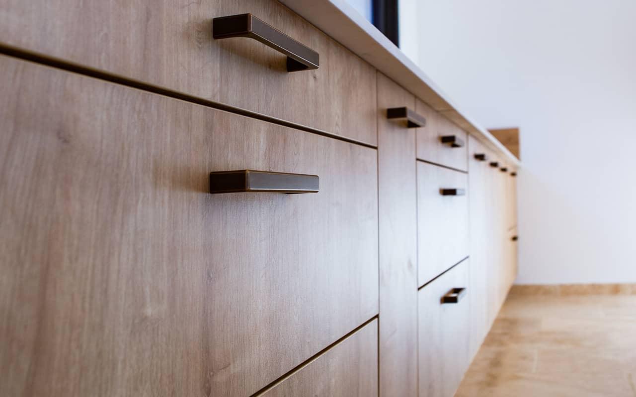 Projet de l'Atelier de Léa : focus sur les façades de placards bois et poignées en fer d'une cuisine contemporaine sur-mesure.