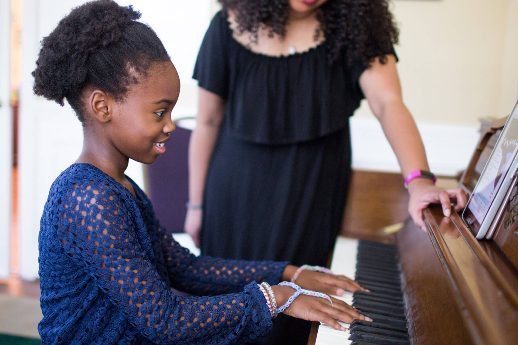 Student playing piano with instructor.