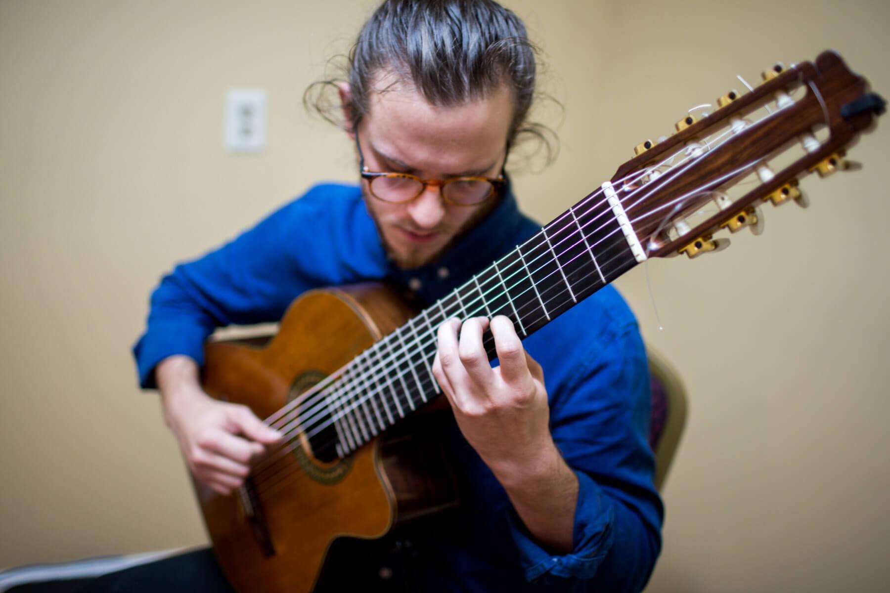 Man plays acoustic guitar, close up.