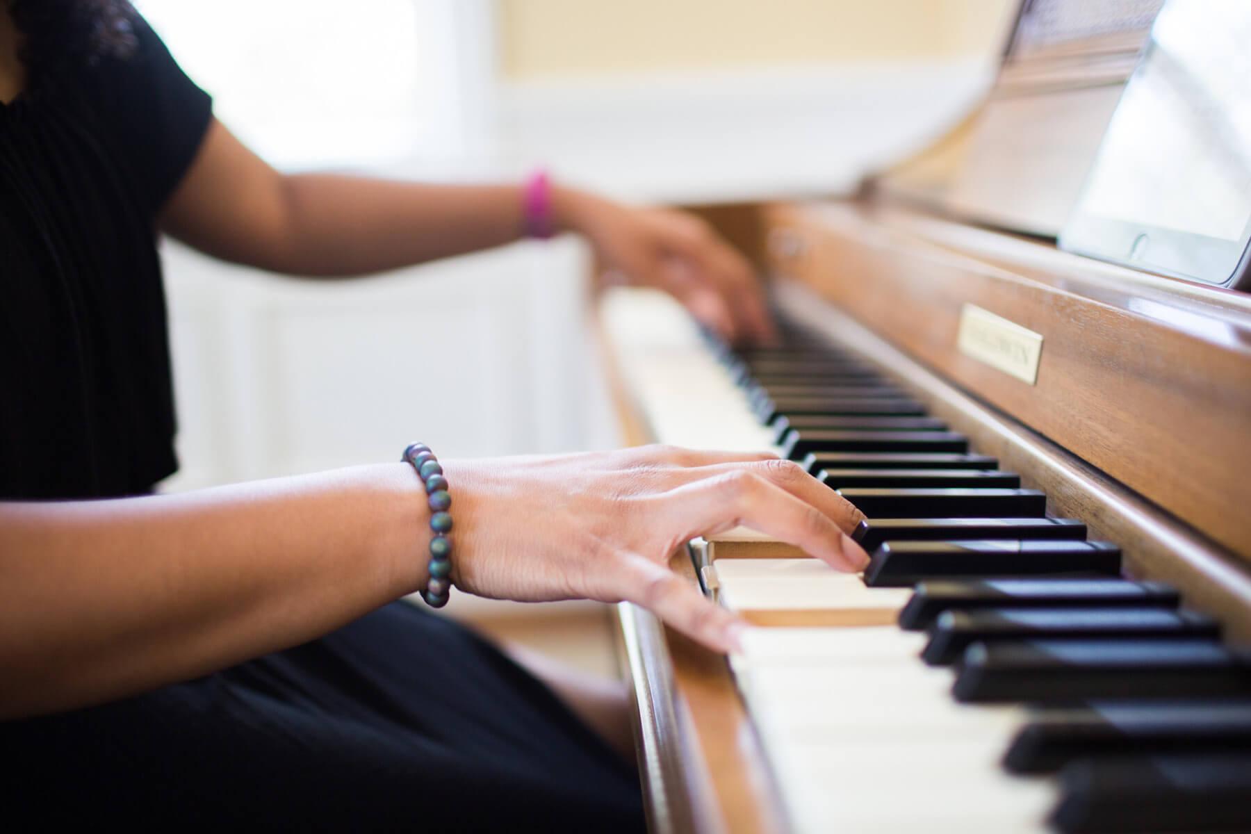 Playing piano, close up shot.