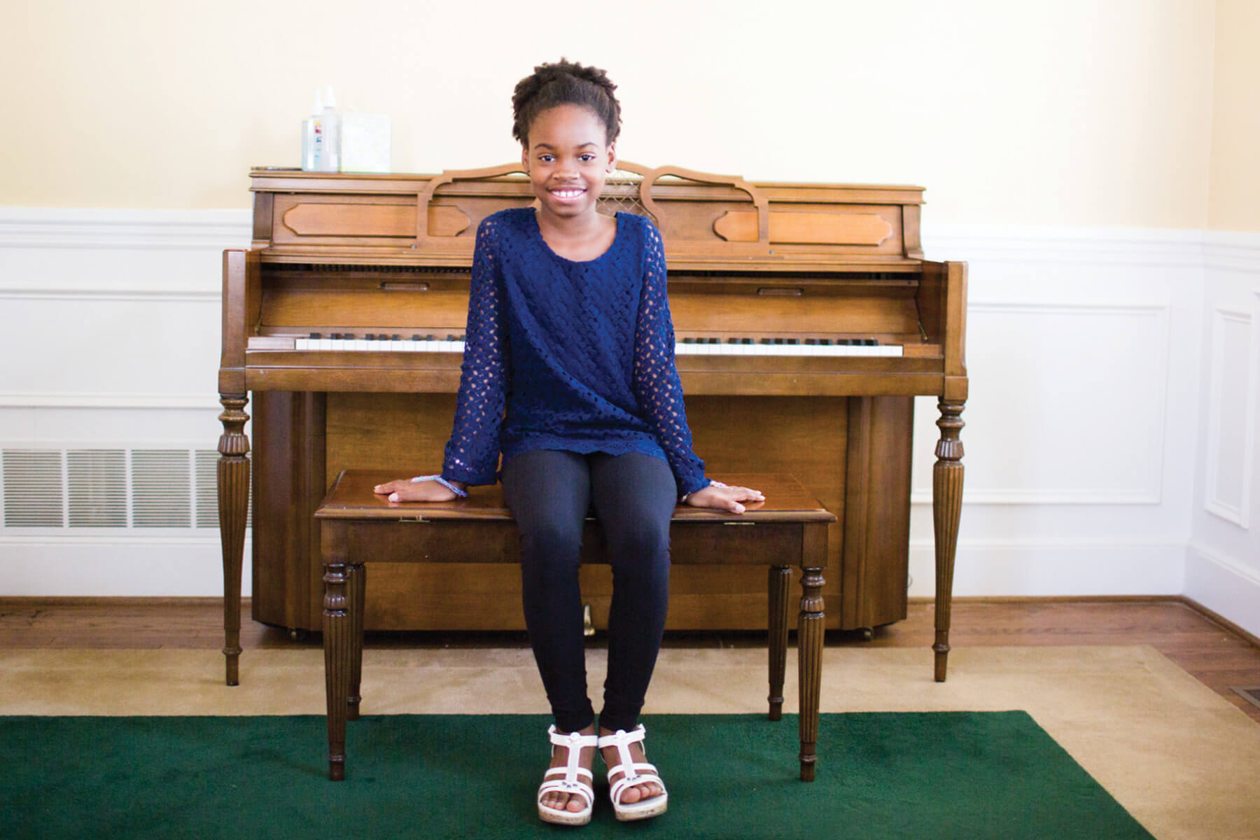 Student sitting on piano bench and smiling.