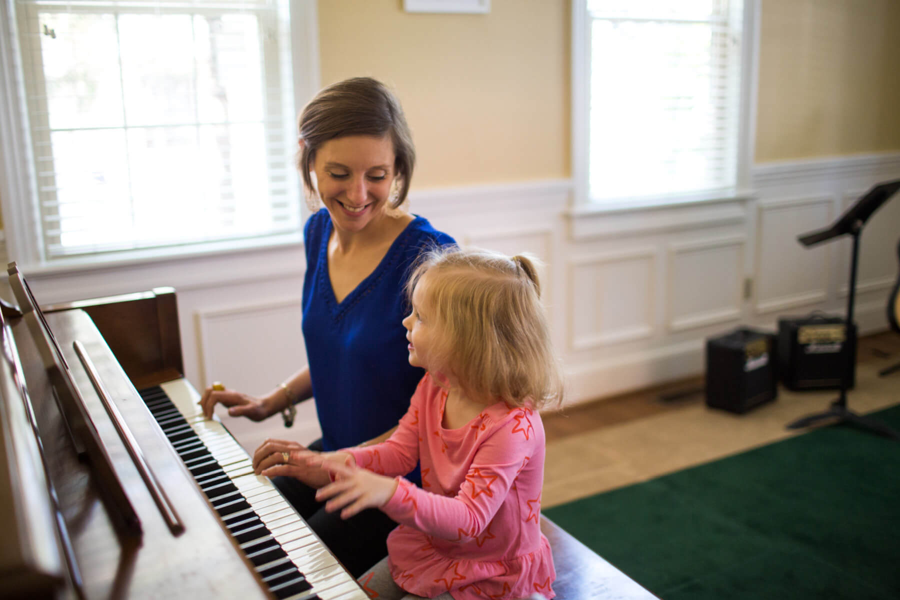 Instructor and young student playing piano