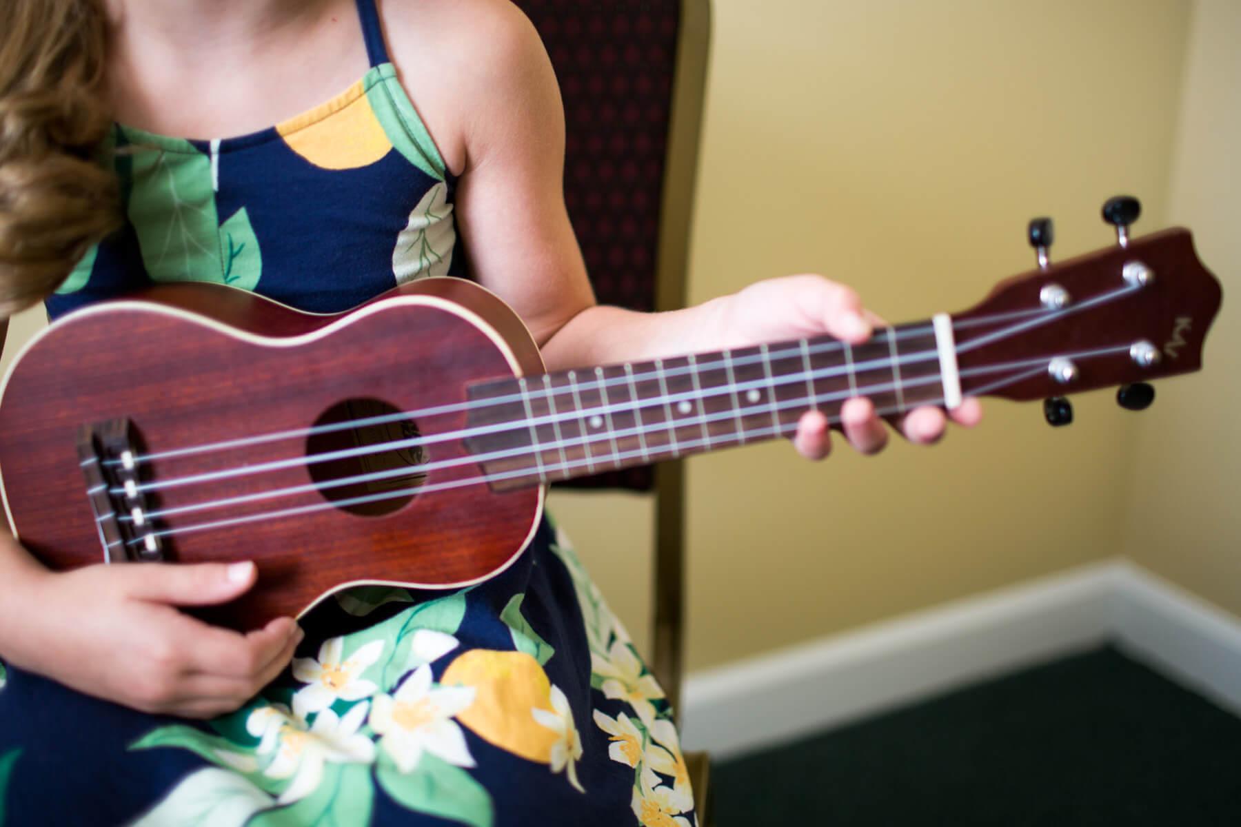 Student plays ukulele, close up shot.