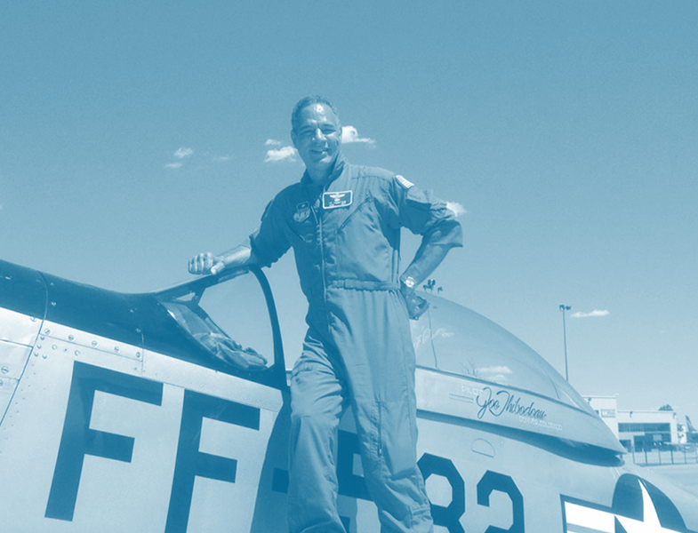 Captain 'T' wearing a flight suit and posed next to a P-51 Mustang World War Two Fighter Plane