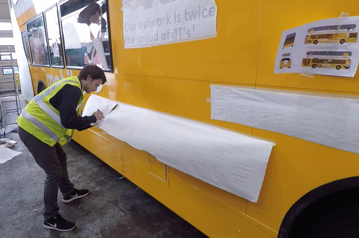 Worker applies double decker full wrap advert
