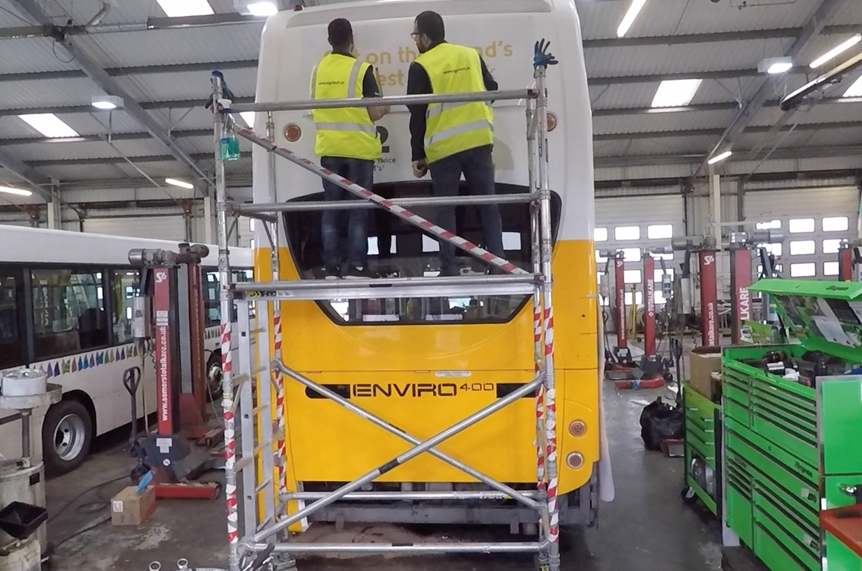 Two workers apply double decker full wrap advert