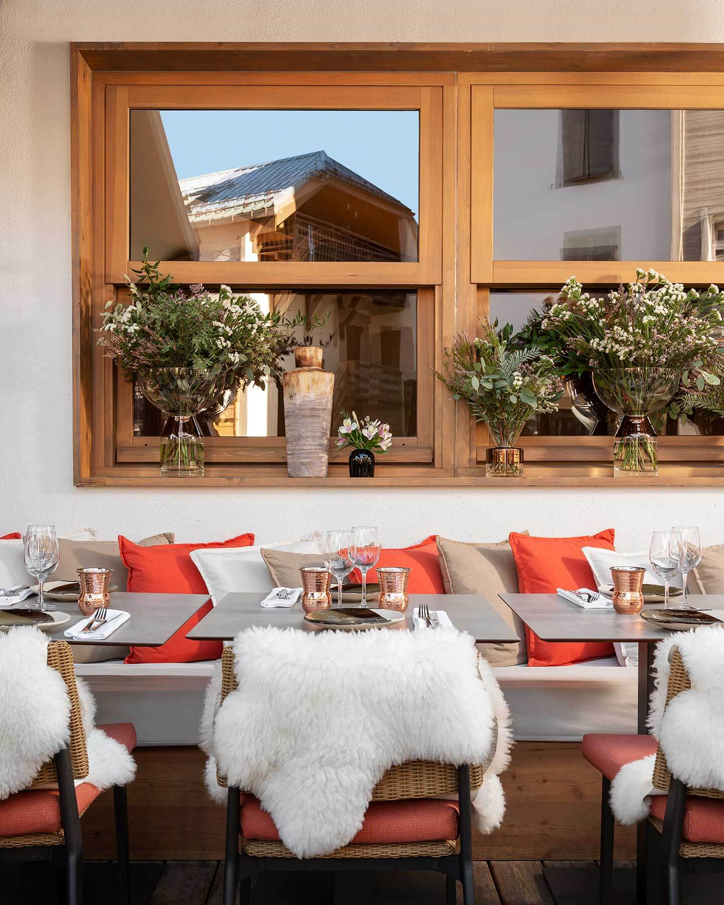Restaurant terrace, bench seat with multicoloured cushions and chairs with white fake fur