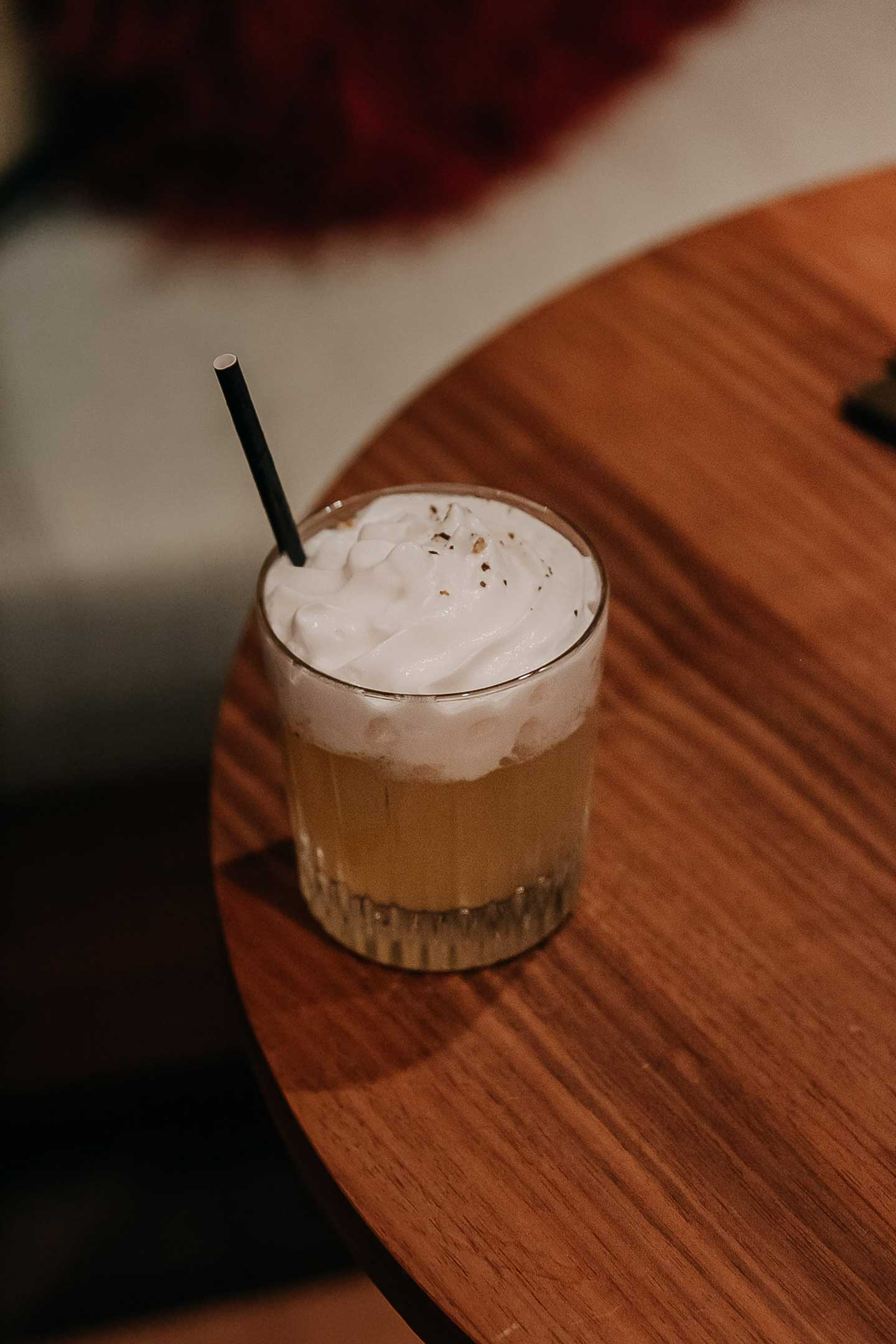 Cocktail whisky sour laid on a wooden table