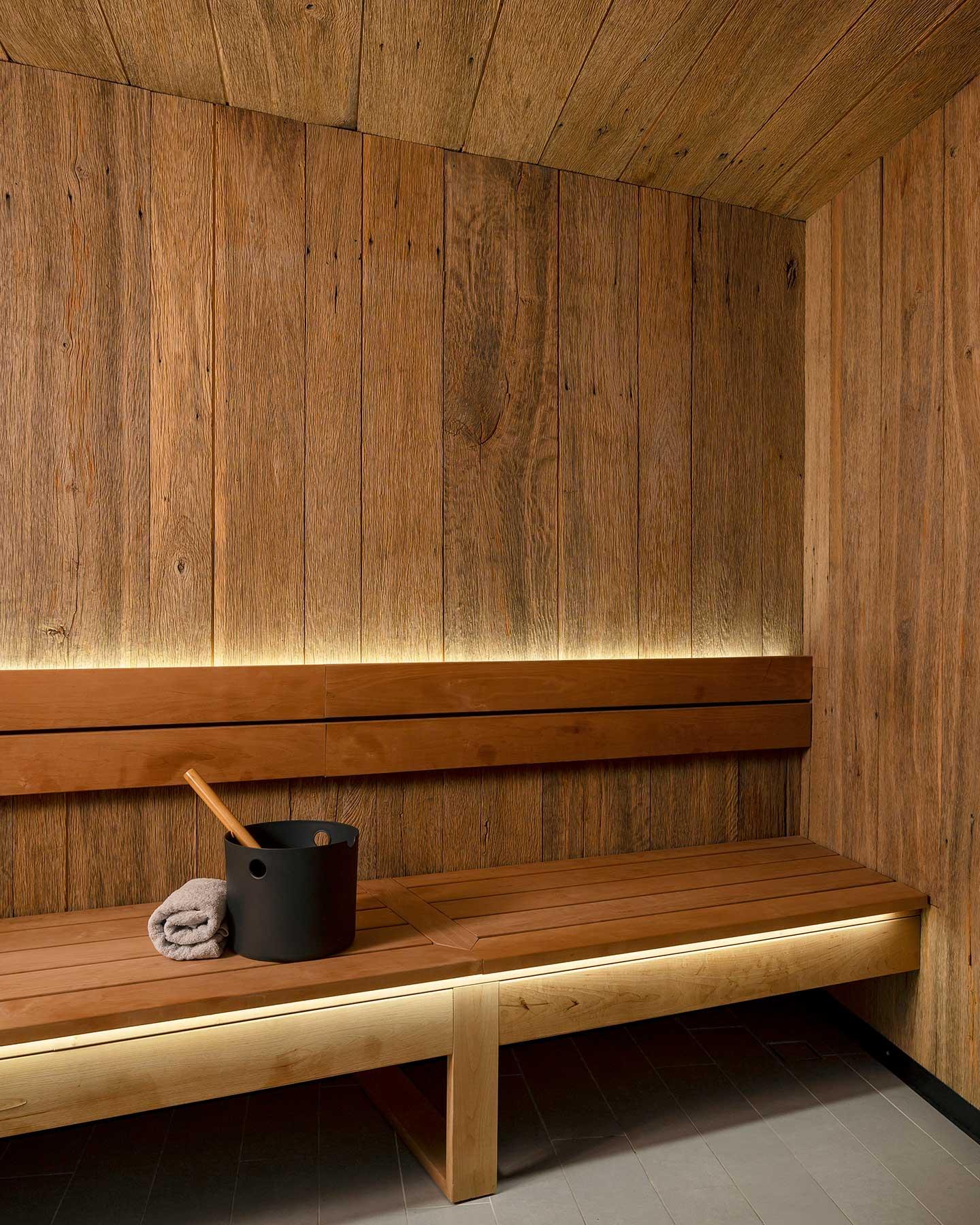 Sauna en bois rétroéclairé avec un sceau et une serviette