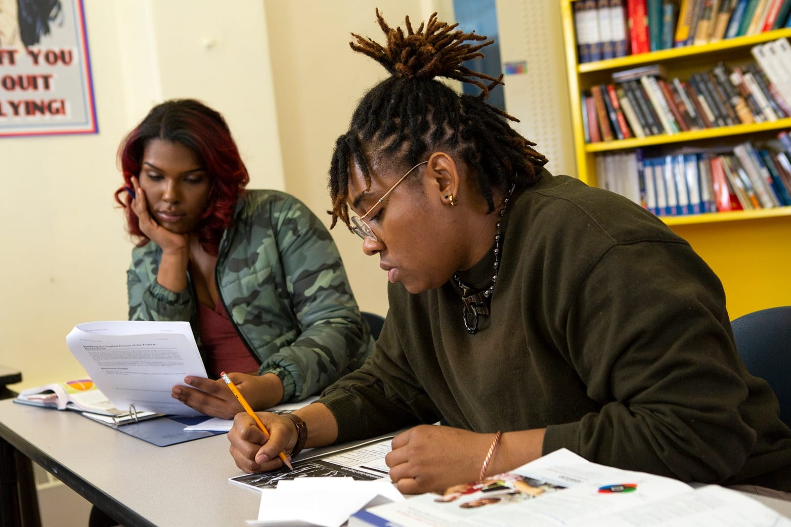 ID: a dark skinned, nonbinary person writes in a notebook while another dark skinned person, with shoulder length hair, with red tips reads a paper.