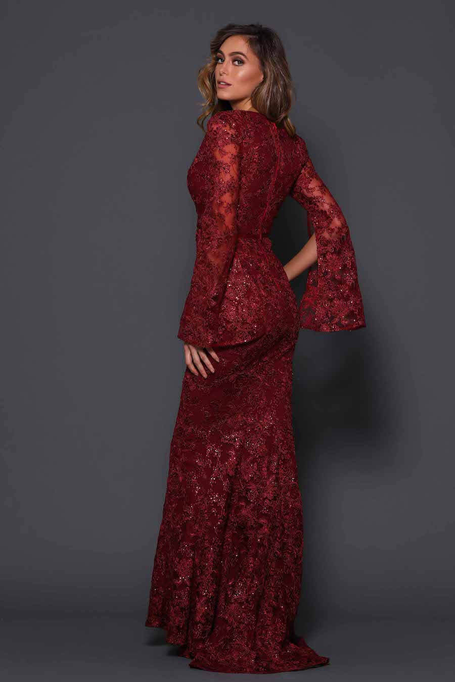 Floor length gown with V neckline and long sleeves in sequinned detail fabric.