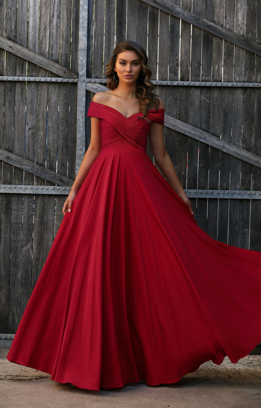 Off the shoulder pleated neckline stretch gown with full skirt.
