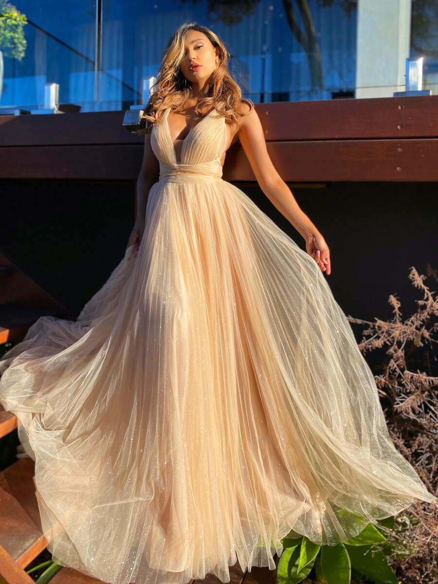Full-length ballgown with glittery tulle and low-cut bodice with versatile shoestring straps that wrap around the waist