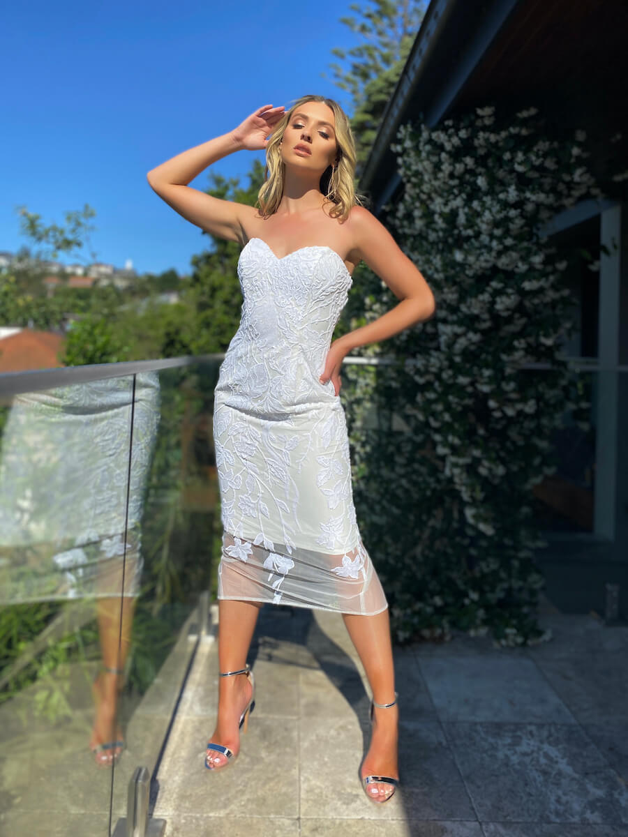 Form fitting midi-length cocktail dress with gorgeous floral sequin detailing and back split