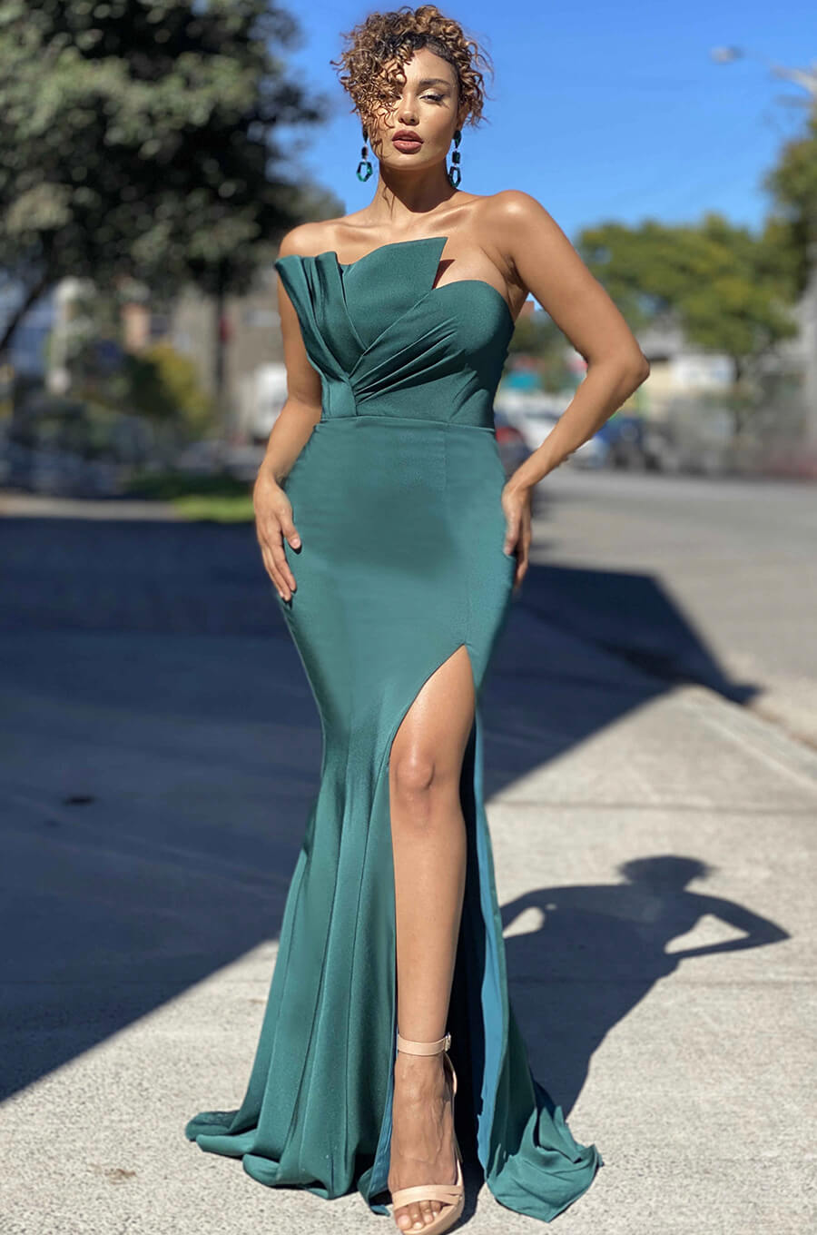 Strapless gown features a fold and pleated bust with mermaid style skirt and side split