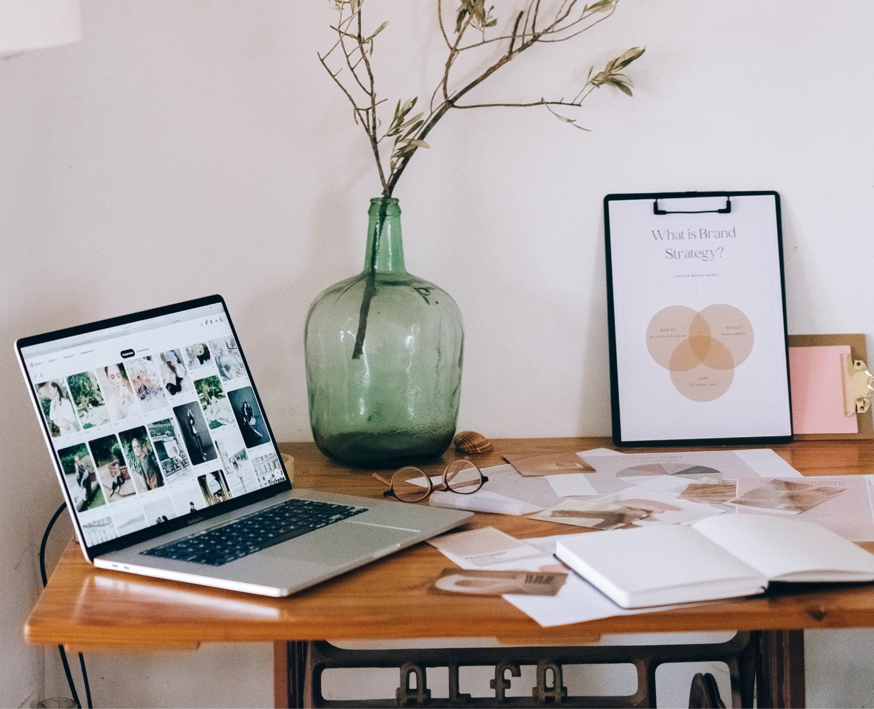 bureau avec ordinateur ouvert sur pinterest, carnet, feuilles imprimées