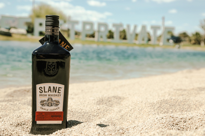 Slane Irish Whiskey bottle on sand