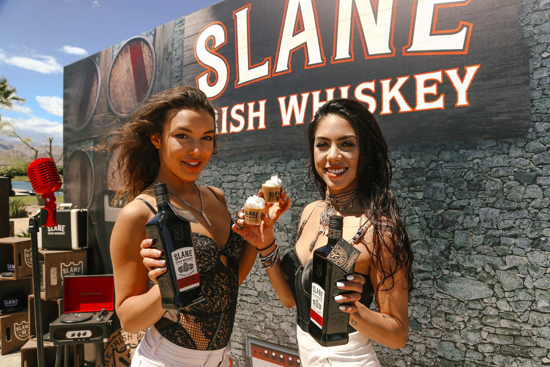 2 girls holding Slane Irish Whiskey bottles