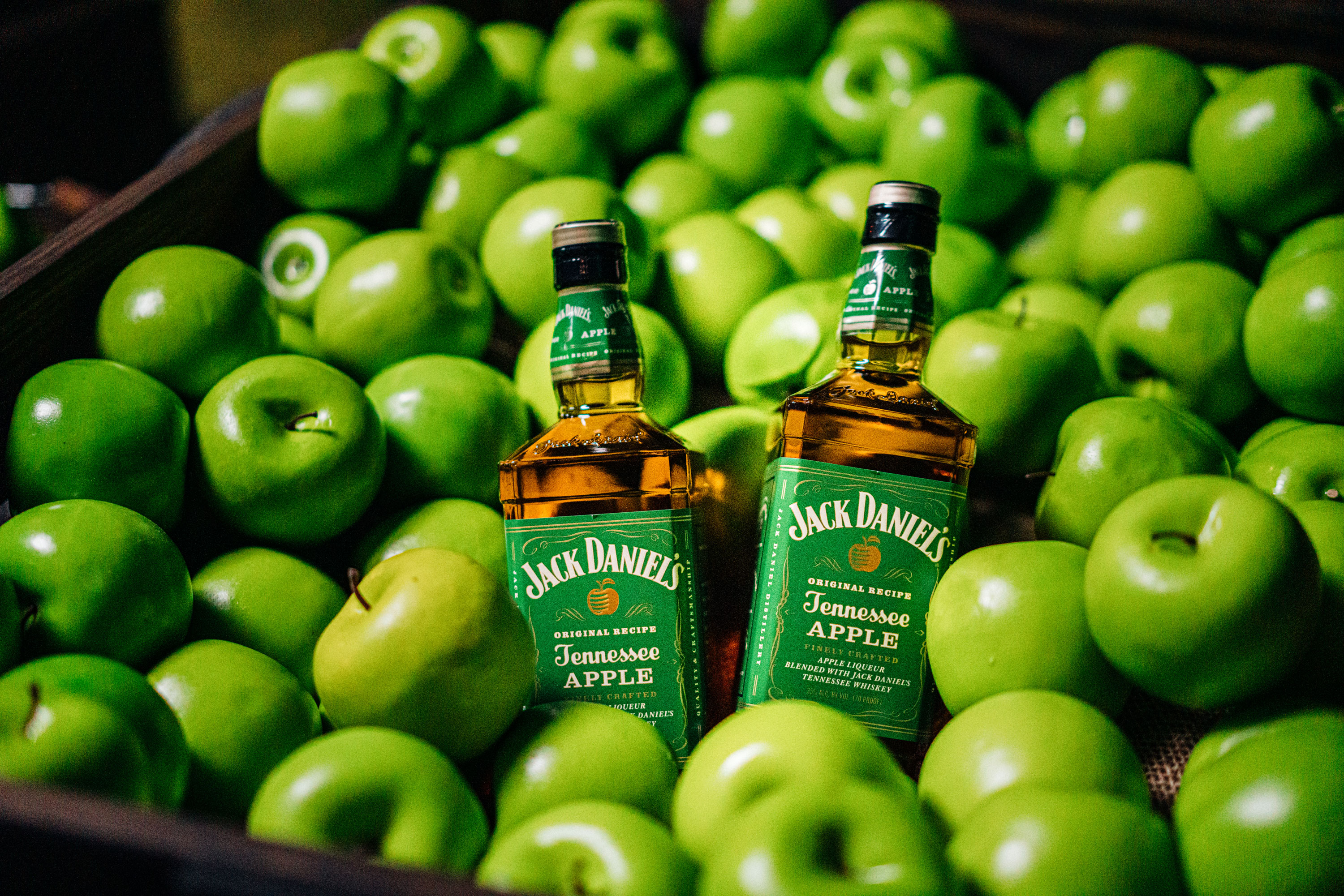 Two Jack Daniels Tennessee Apple bottles in a basket of green apples