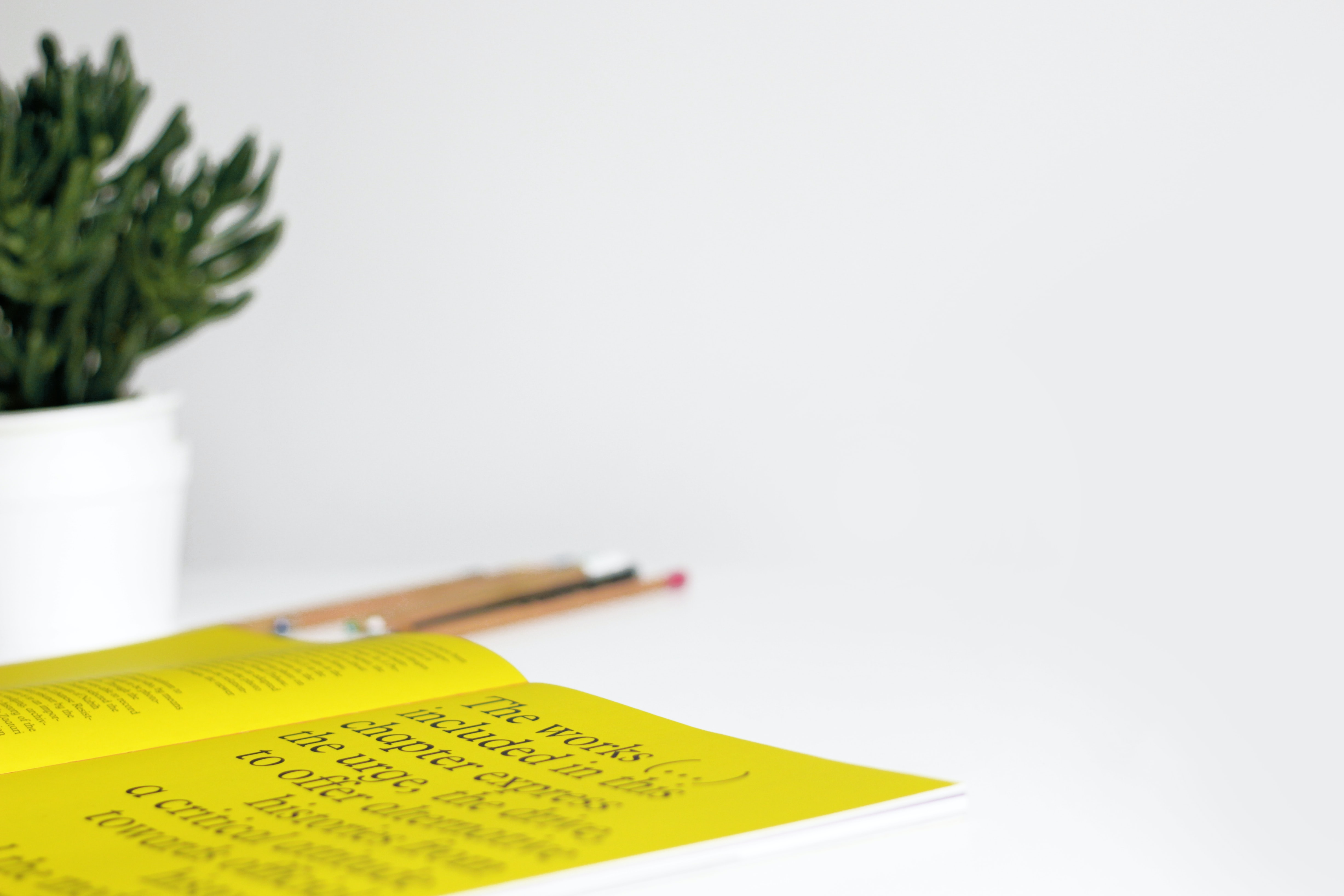 A picture of a white desk, with on the left a plant and on the desk a book with yellow pages and pencils laying next to it.