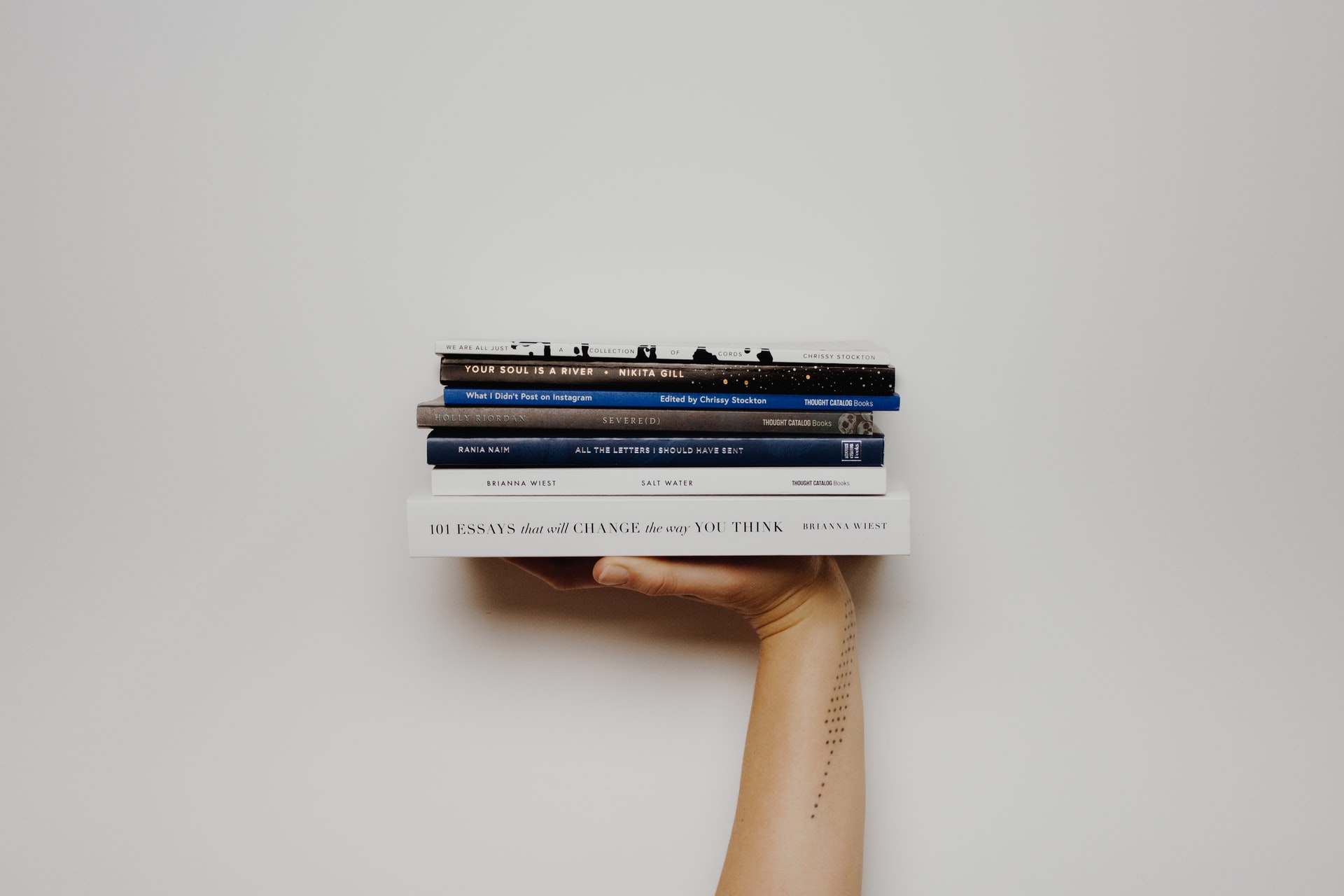 A person's hand holding up a pile of books with a white background