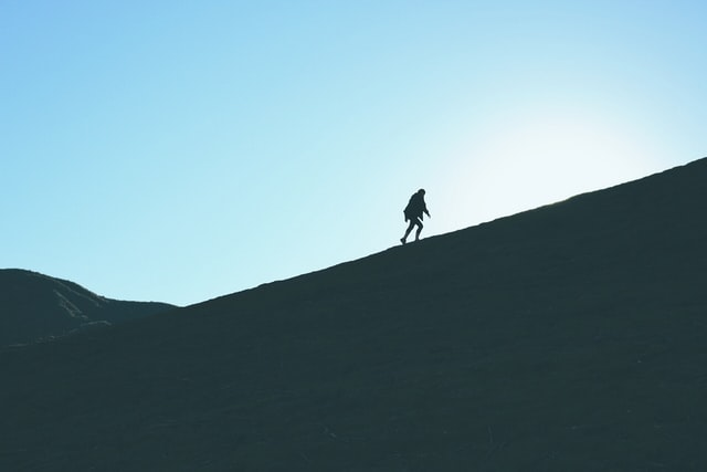 A man walking up a mountain with a blue sky in the background