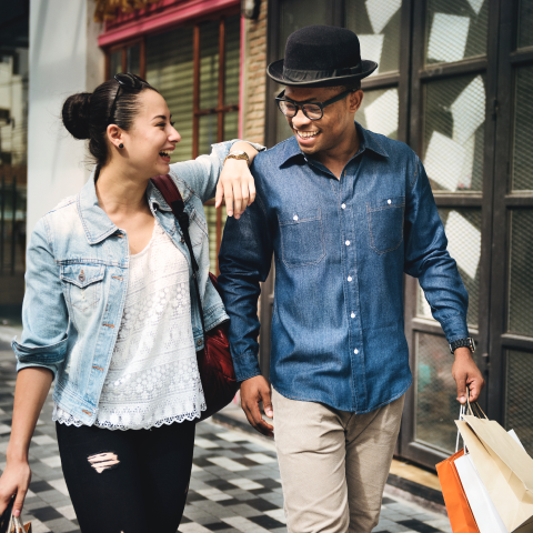 Couple walking along the street with shopping bag image