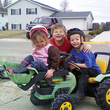 Kids playing outside on a toy tractor