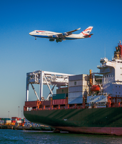 Freight cargo flying over a loaded ship