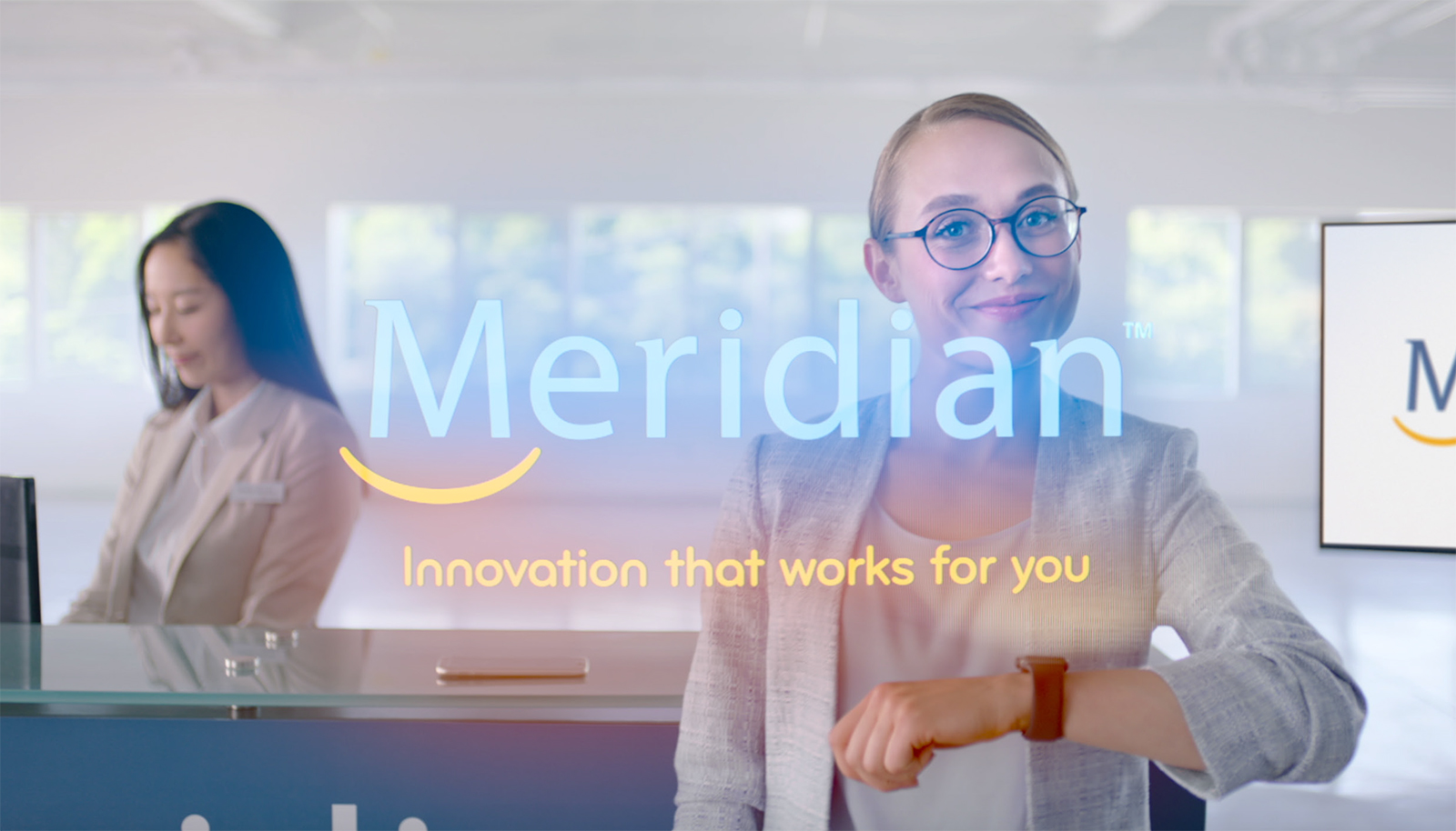 Young blonde woman wearing glasses looking at her watch, riding on a golf cart in a Meridian branch, looking at her phone, taking a photo of a giant cheque and then standing in front of a branch counter.
